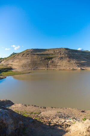 sand quarry: Sand quarry with a pond against blue sky