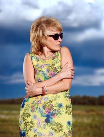 shiver: Portrait of middle aged woman standing outdoors