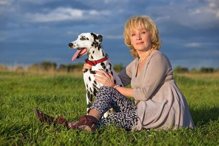 mid adult women: Middle aged woman and her Dalmatian dog on summer meadow Stock Photo