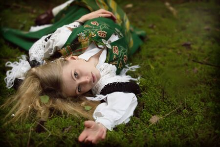 the enchantress: Young girl lying on the ground in the forest