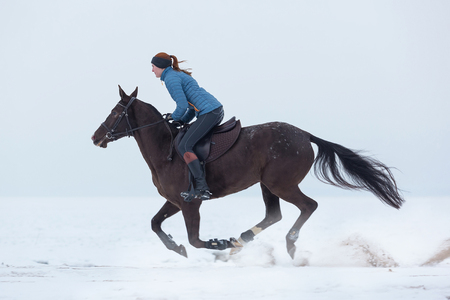 Young woman riding horse at winter day Stock Photo