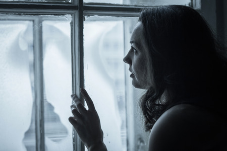 Beautiful sad girl looks in a frozen window Banque d'images