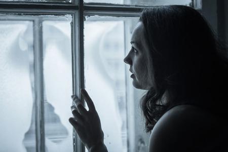 Beautiful sad girl looks in a frozen window Stock Photo