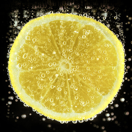 Lemon slice in water on black background