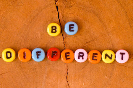 be different: Colored be different on wooden background