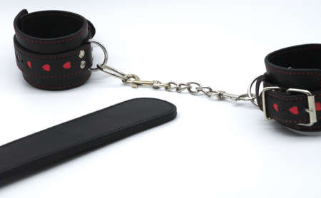 leather handcuffs with chain and ball gag isolated in the white and spanker background Standard-Bild