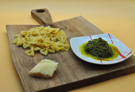 everything you need ready to cook an appetizing pasta farfalle with Genoese pesto with the perfect Italian recipe, all placed on an elegant cutting board of noble wood