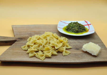 everything you need ready to cook an appetizing pasta farfalle with Genoese pesto with the perfect Italian recipe, all placed on an elegant cutting board of noble wood Archivio Fotografico