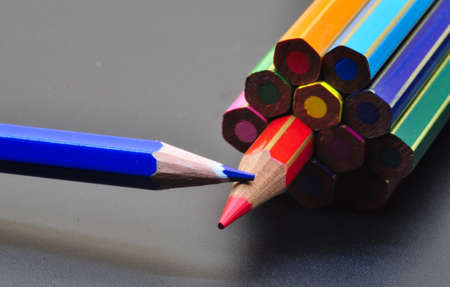 metaphor of strategy and teamwork shown by color pencils on black background, representing the concept of thinking outside the box.