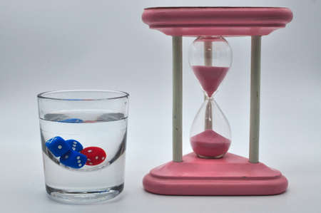 glass of alcohol containing red and blue dice with gorgeous vintage pink hourglass on white background