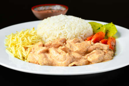 beef stroganoff served with white rice, potato straw and cooked vegetables
