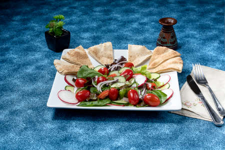 fattoush an arab salad served on a white plate on a blue background