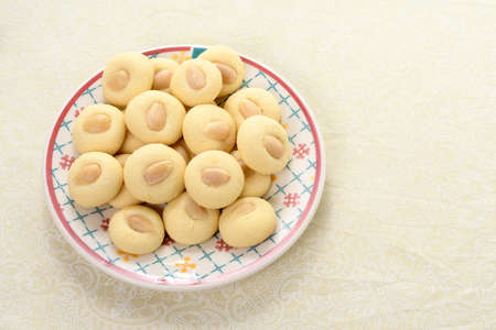 Graibe a buttery Arab biscuit with an almond on a plate