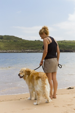 caresses: Girl on the beach with his dog Cantabria Stock Photo