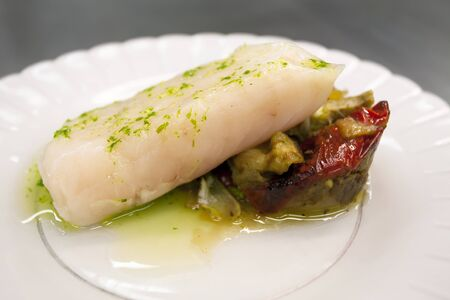 hake: Hake in green sauce with sauteed vegetables Stock Photo