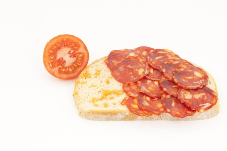 Bread with tomato and sausage Iberico on a white background Stock Photo - 13060535
