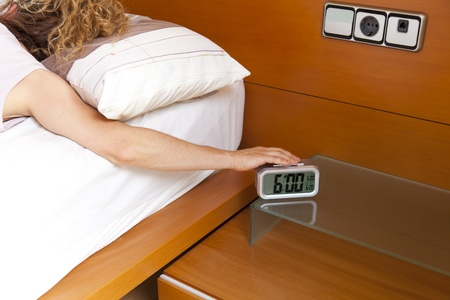 Girl turning off the alarm clock at 6 oclock in the morning Stock Photo