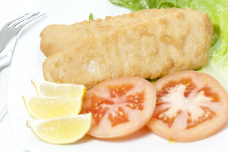 hake: Delicious breaded hake fillets with tomato garnish Stock Photo