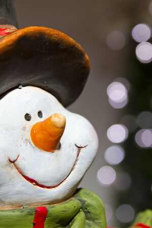 Snowman decoration on a background of Christmas lights photo
