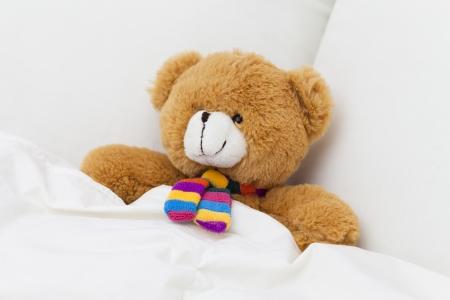 Teddy bear sleeping in a bed