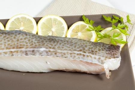 Fresh cod fillet with fresh lemon slices Standard-Bild