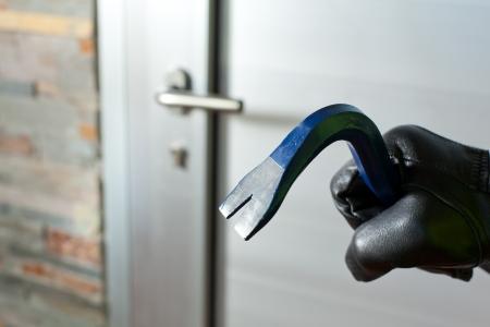 Ladr�n con una barra de hierro en la mano para abrir la puerta