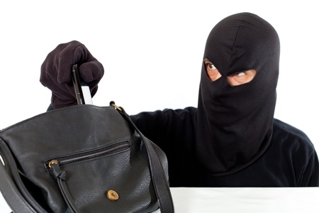 Thief stealing a telephone of the purse of a girl photo