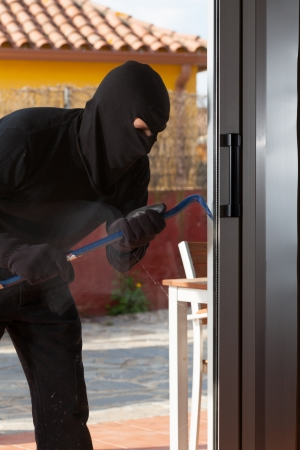 Thief trying to force a window to rob a house Stock Photo - 20279756