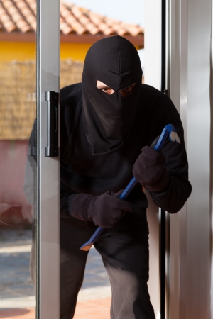 law breaker: Thief trying to force a window to rob a house