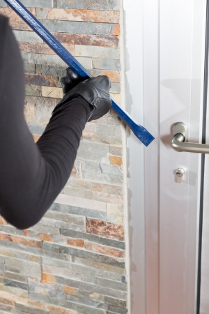 Thief with a bar of iron in the hand to open a door photo