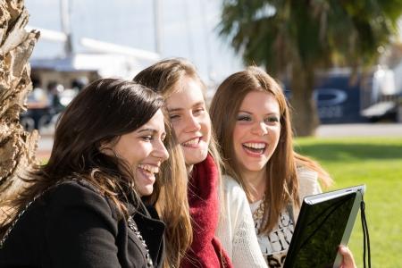 Estudiantes mujeres j�venes consultados en una tableta
