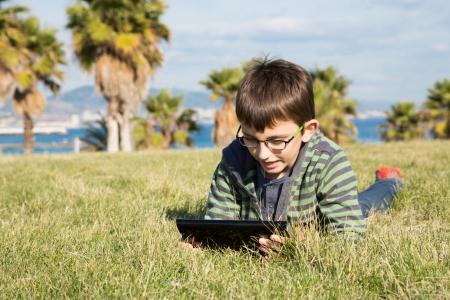 portative: Ragazzo con un computer portatile sdraiata sul prato in un parco Archivio Fotografico