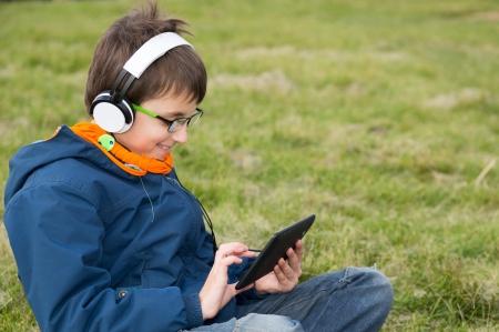 portative: Ragazzo con un computer portatile sdraiato sul prato in un parco