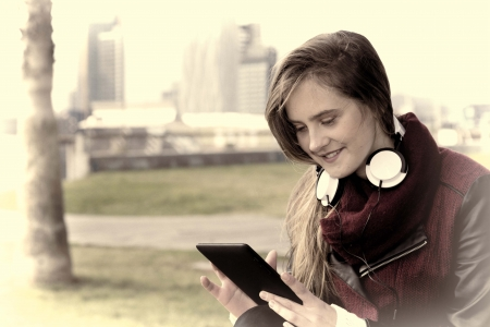 Pretty girl listening to music on a tablet photo