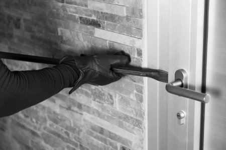 burglar: Thief with a bar of iron in the hand to open a door