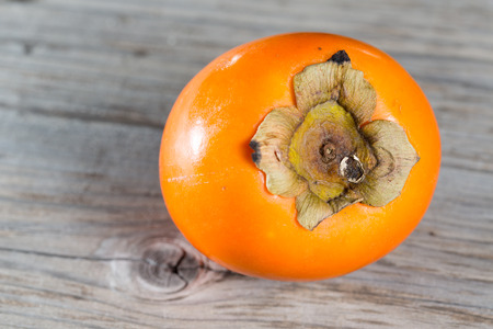 red skinned: Closeup of fresh persimmon on a wooden table Stock Photo