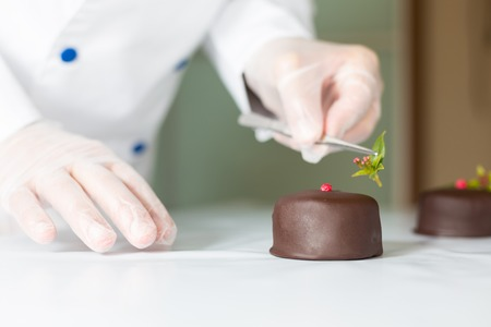 restaurateur: Confectioner putting the last ornament to a cake