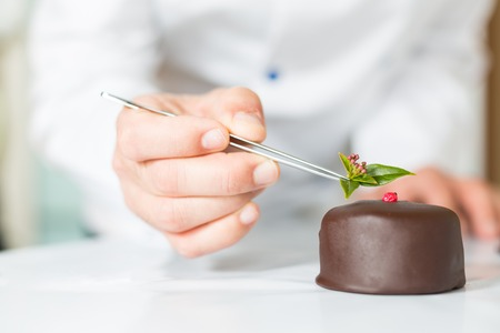 Confectioner putting the last ornament to a cake photo