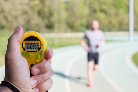 Entrenador marcando veces en una pista de atletismo Foto de archivo