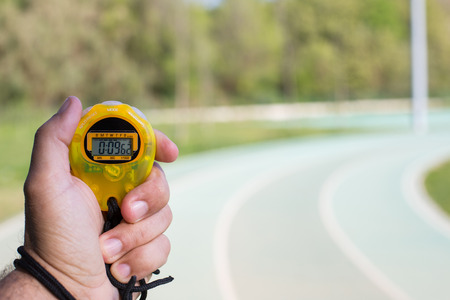 Coach clocking times in a running track photo