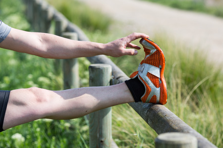 loosen up: Runner doing stretching leg on a fence