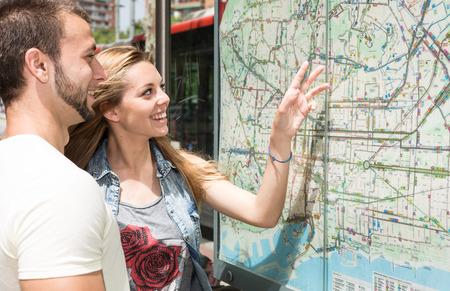 Pareja joven que consulta un mapa de la ciudad de Barcelona