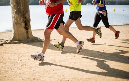 Grupo de personas haciendo atletismo junto a un lago Foto de archivo