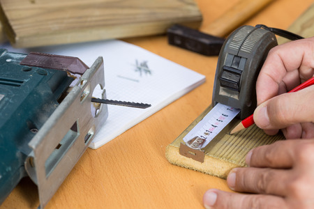 wooden metre: Carpenter taking action on a wooden slat Stock Photo