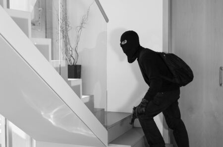 assail: Thief stealing private house with a gun in hand Stock Photo