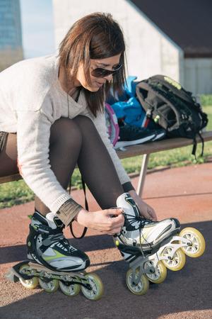 rollerskater: Woman preparing to skate in the park