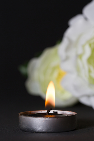 lament: Black candle with black background and white rose Stock Photo