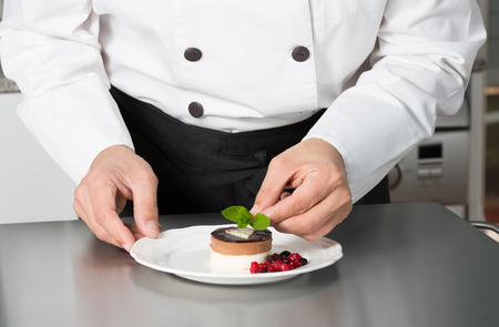 Chef decorating a homemade mousse with berries