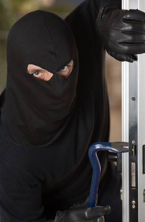 Thief entering a private home to steal