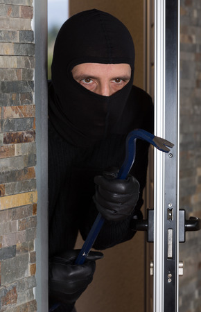 household insurance: Thief entering a private home to steal